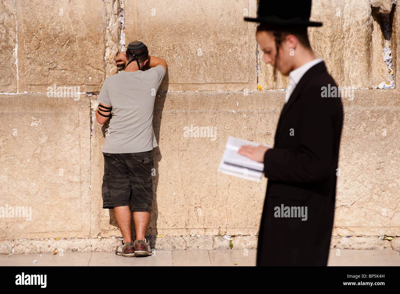A Jewish young man prays at the Western Wall while an orthodox worshipper passes reading a prayer book. - Stock Image