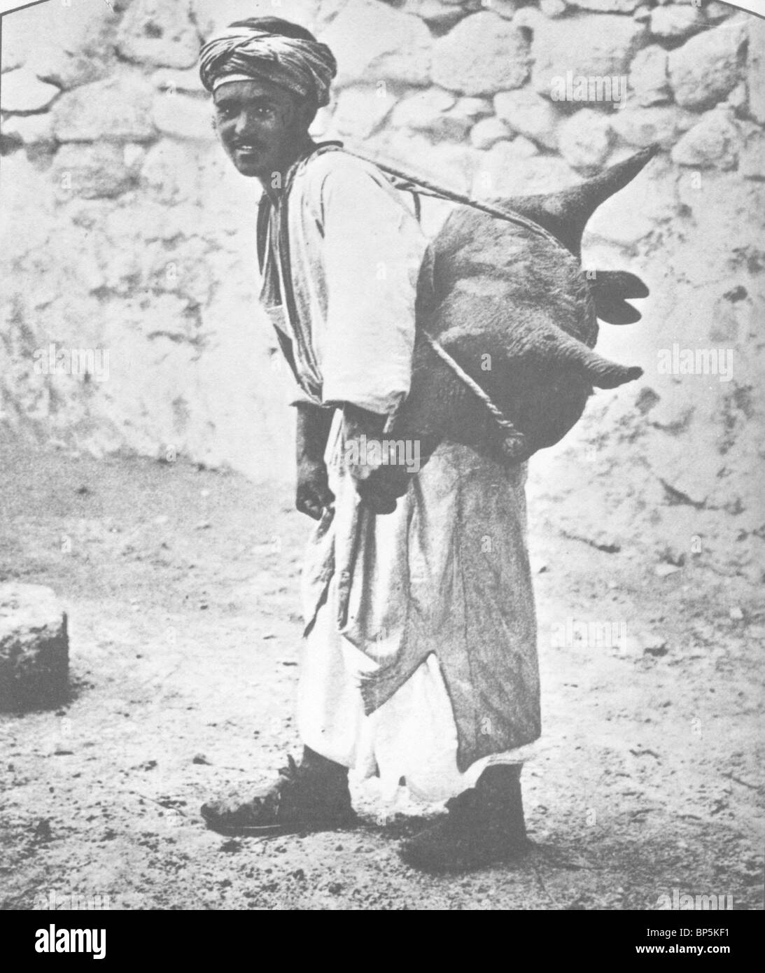 WATER CARRIER, JERUSALEM AT THE BEGINING OF THE 19TH. C. WATER IS CARRIED IN SHEEP OR GOAT SKINS FROM THE FEW WELLS - Stock Image