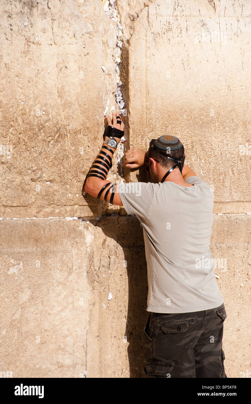 A Jewish young man wearing kippah and tefillin prays at the Western Wall in Jerusalem's Old City - Stock Image