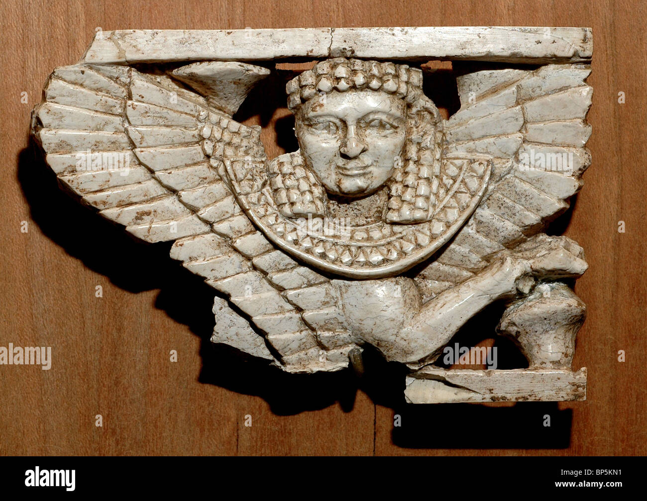 Ivory plate depicting a sphinx a winged creature with the body of a lion & a human head. Phoenician carving - Stock Image