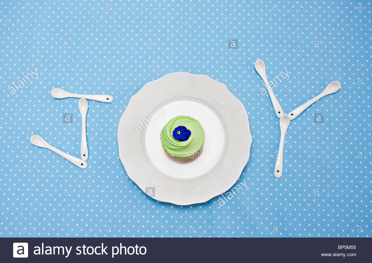 Teaspoons and plate with cupcake spelling 'joy' on tablecloth - Stock Image