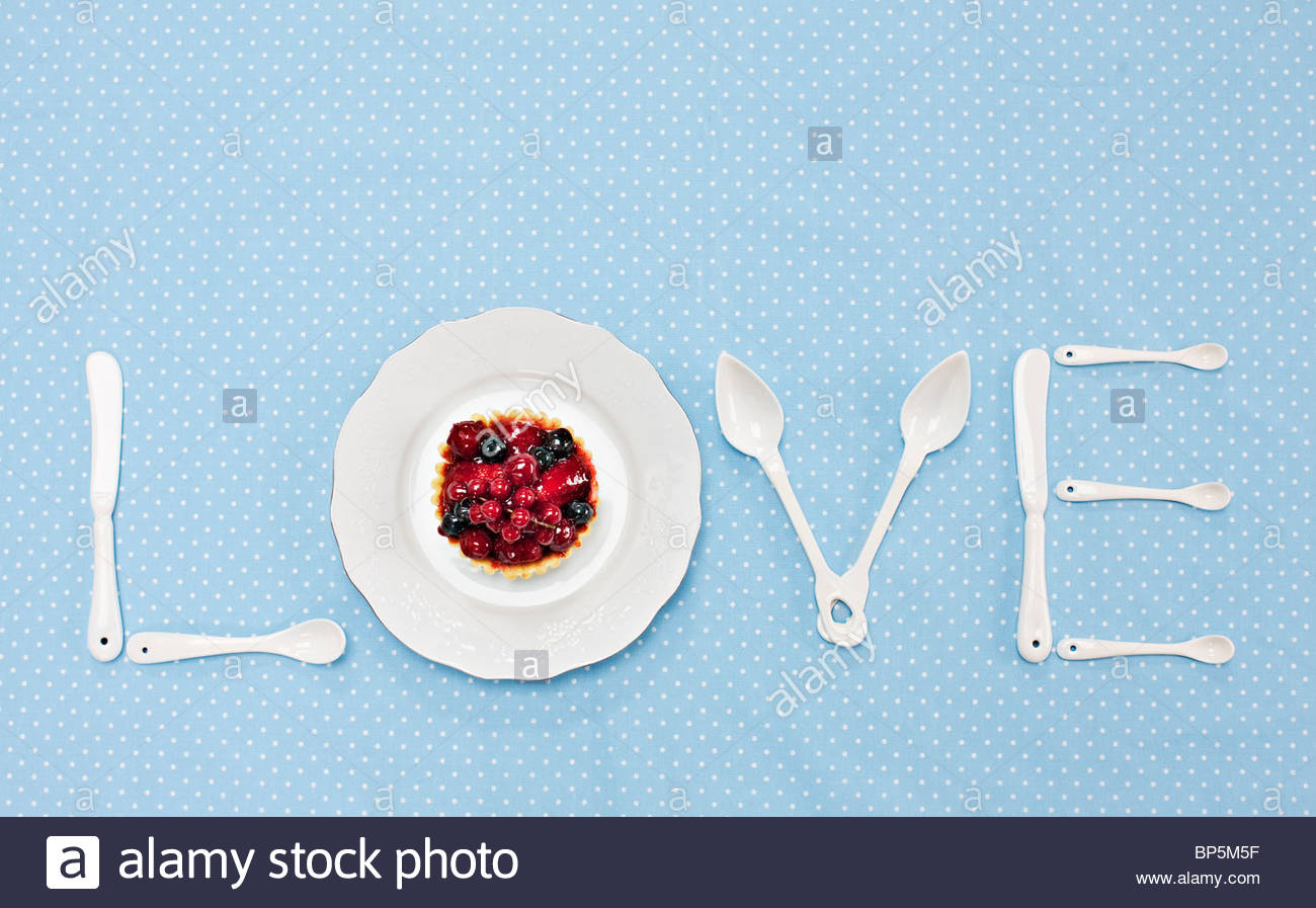 Silverware and plate with tart spelling 'love' on tablecloth - Stock Image