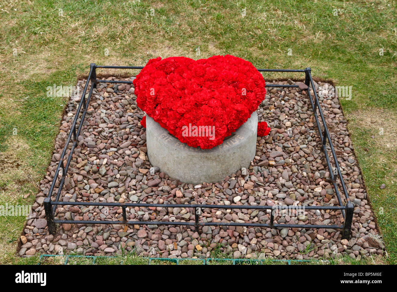 Heart-shaped arrangement of red carnations covers the burying place of the heart of Robert the Bruce, Melrose Abbey, - Stock Image