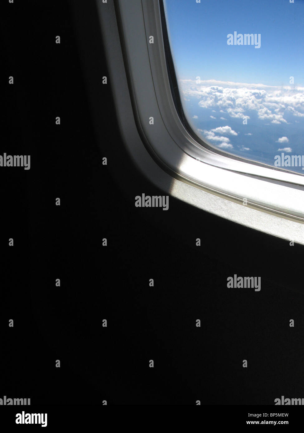 A passenger's view of an airplane's window outside, daylight with blue sky and clouds - Stock Image