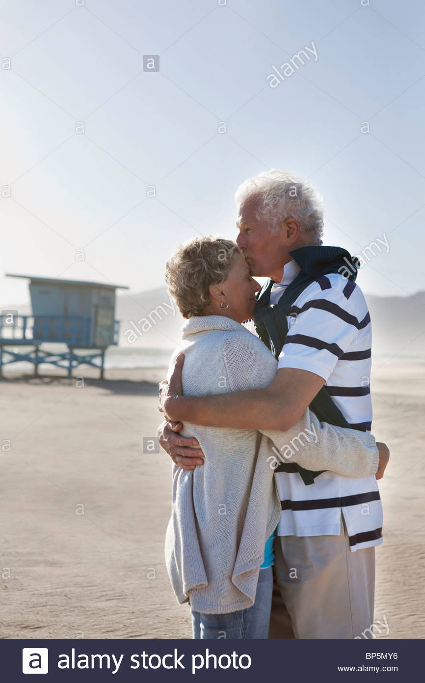 Senior couple hugging and kissing on beach - Stock Image