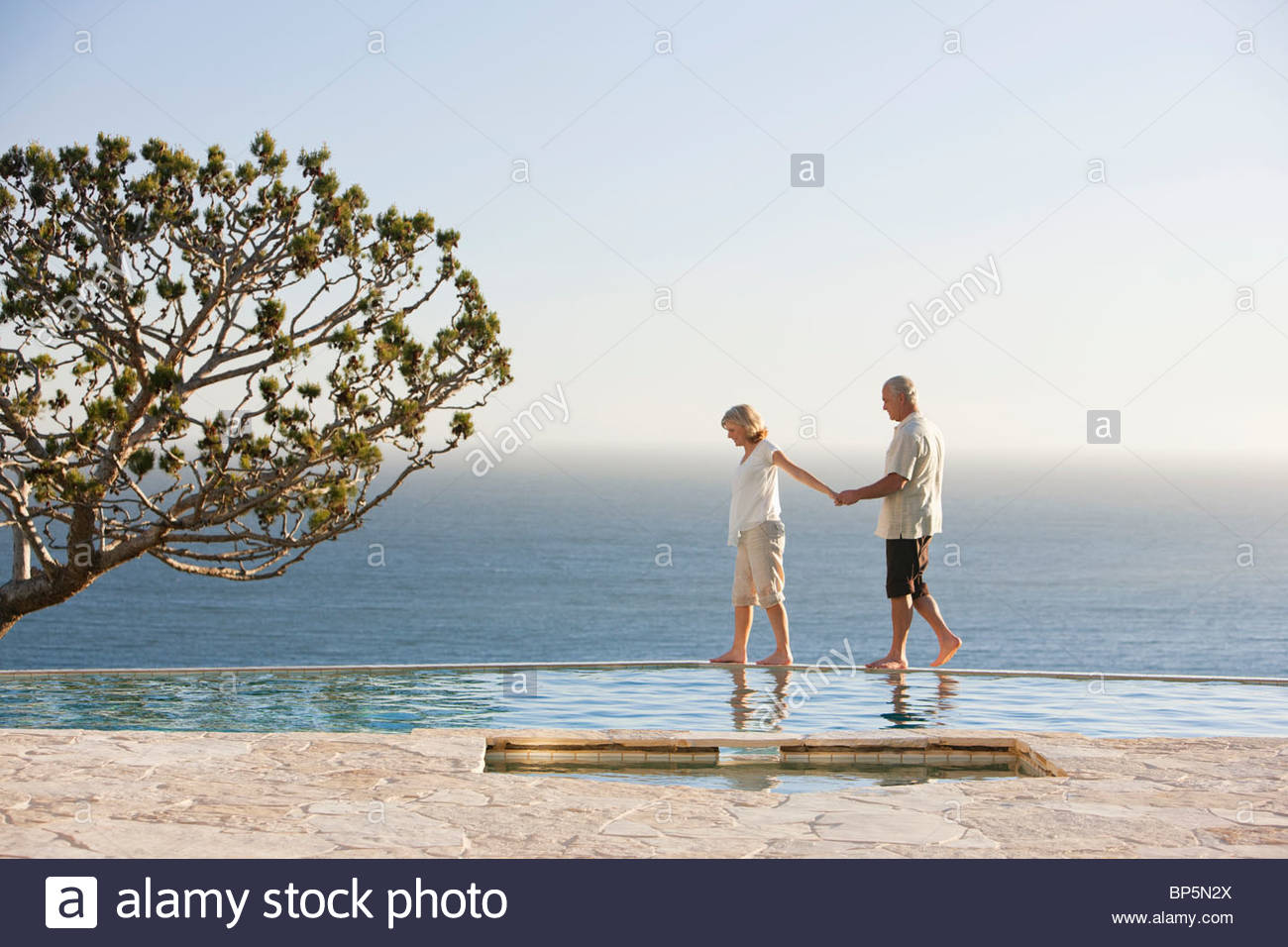 Senior couple holding hands along edge of swimming pool overlooking ocean Stock Photo