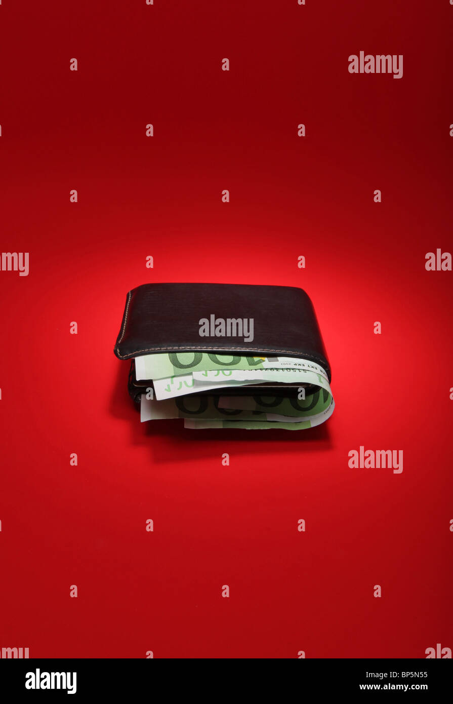 A black leather wallet with money on a bright red background, currency is 300 Euros - Stock Image