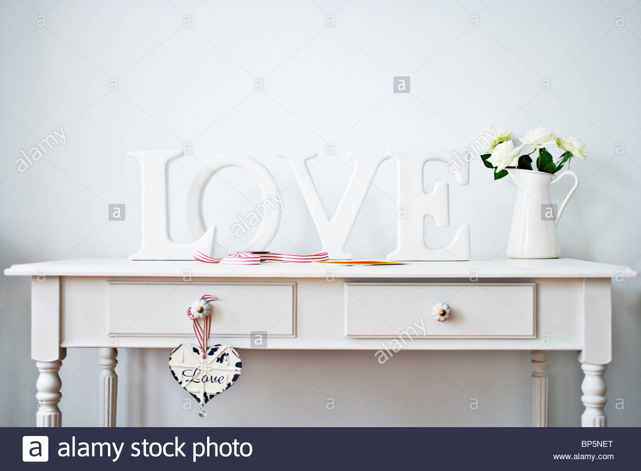 'Love' decorations, ribbon, roses and card on desk - Stock Image