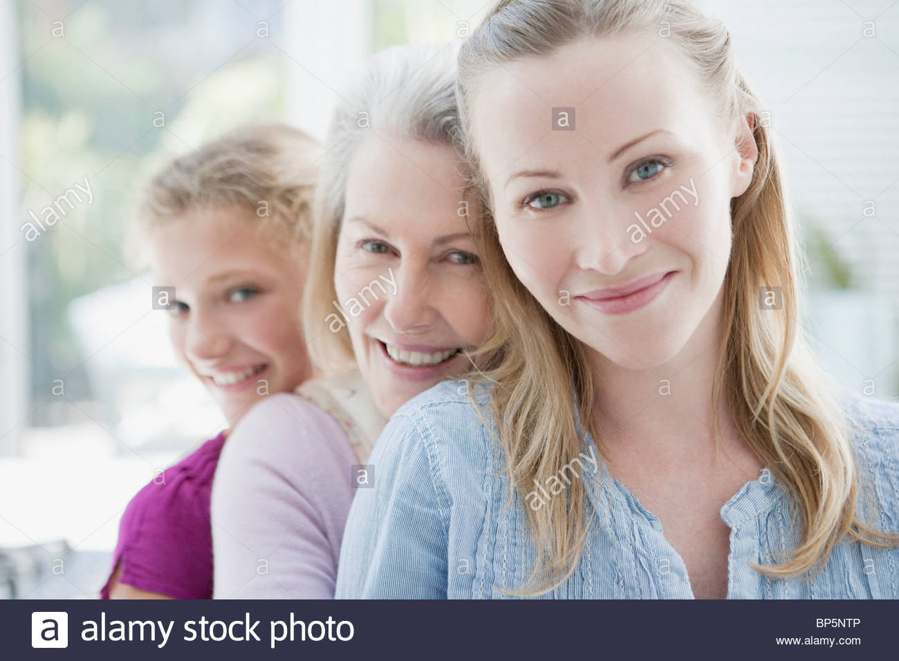 Smiling grandmother, mother and daughter hugging - Stock Image