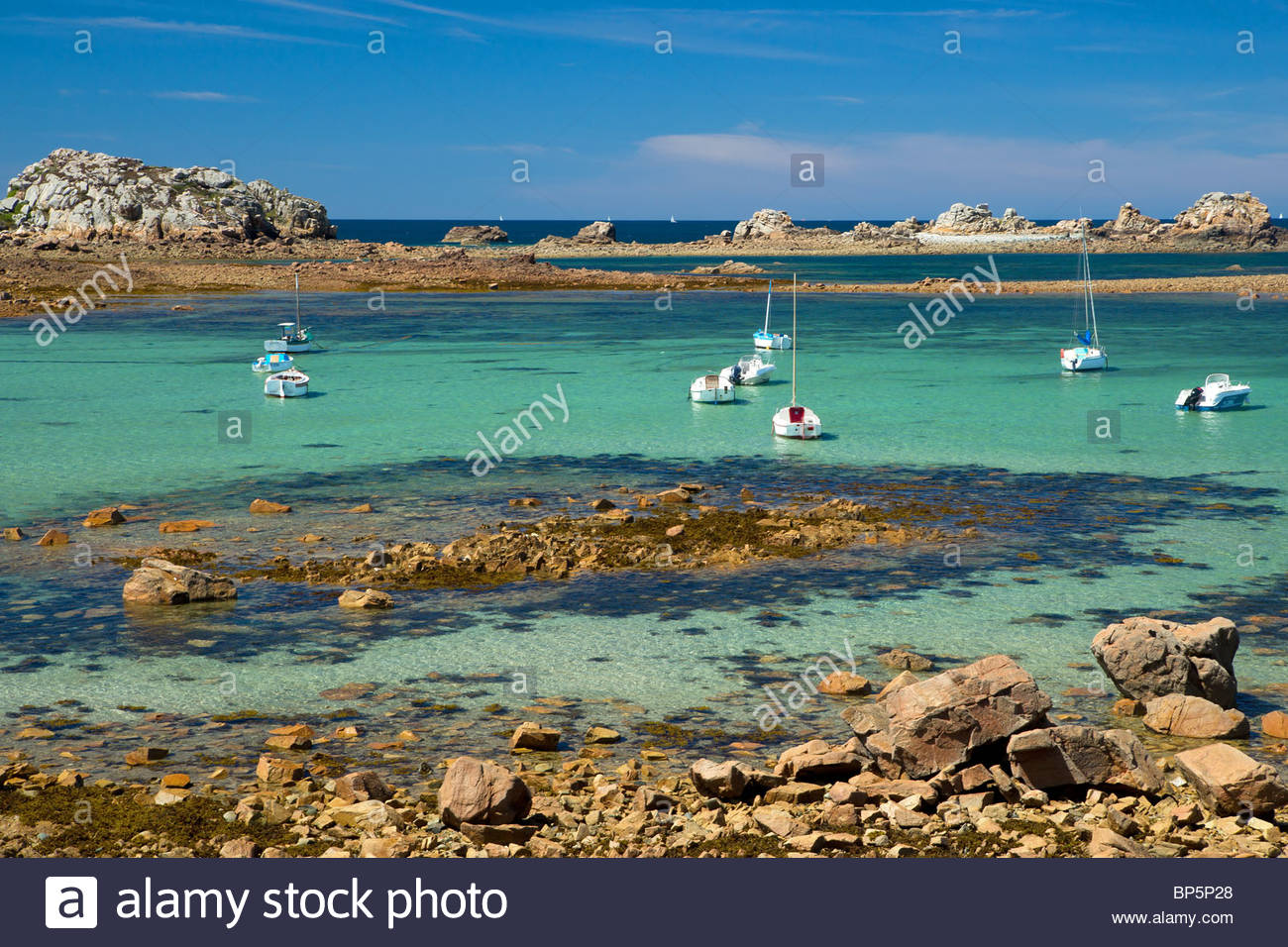 Boats and clear water between pink granite rocks at Plougrescant (near Perros Guirec) in Brittany - France - Stock Image