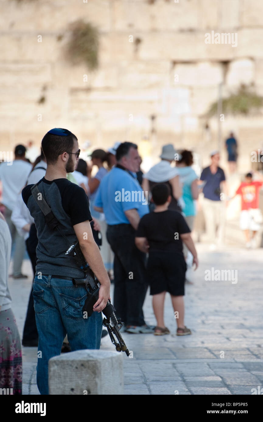 An Israeli armed with an assault rifle visits the Western Wall in Jerusalem's Old Cit - Stock Image