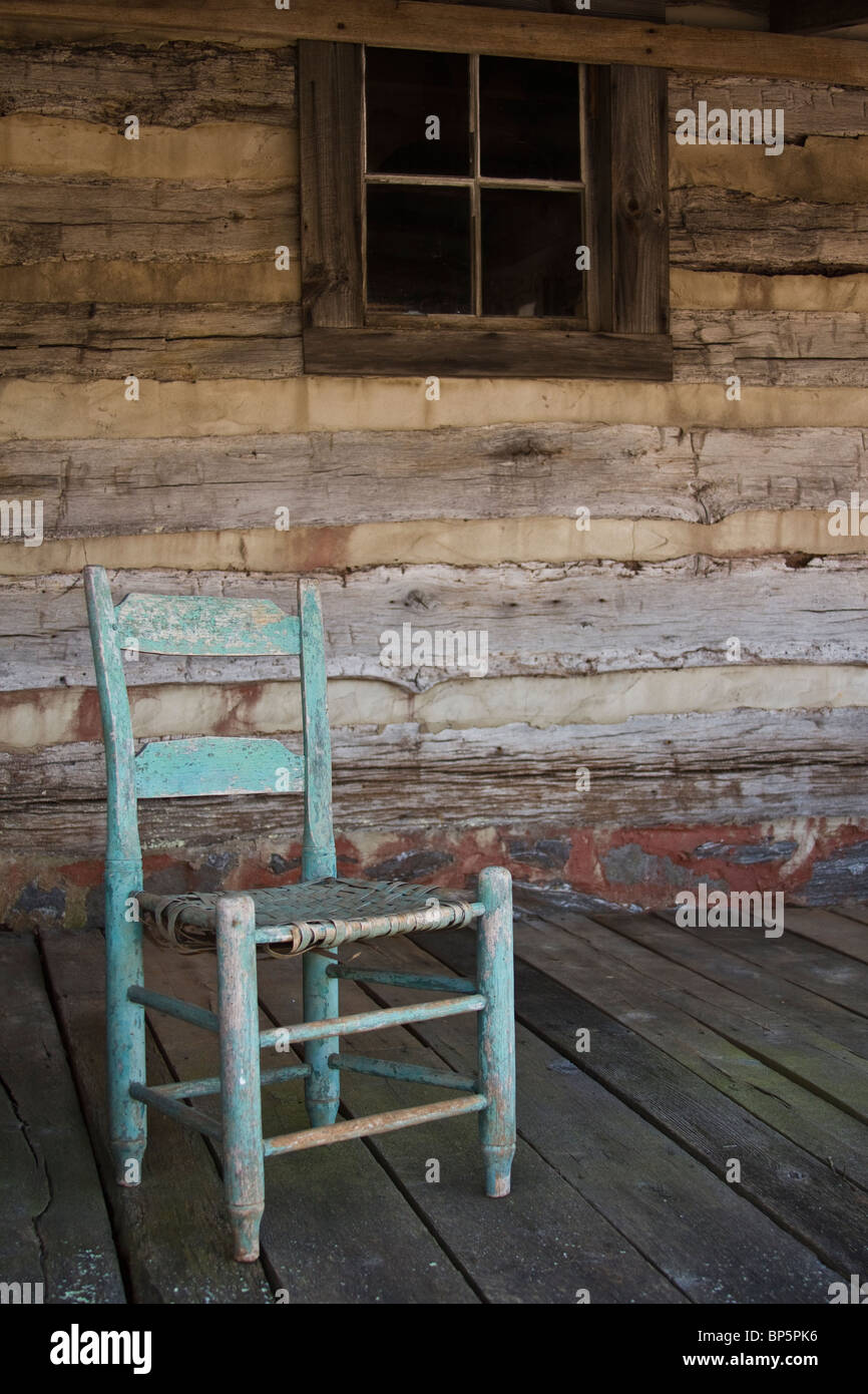 Old Antique Rocking Chair On Wooden Deck Of Log Cabin