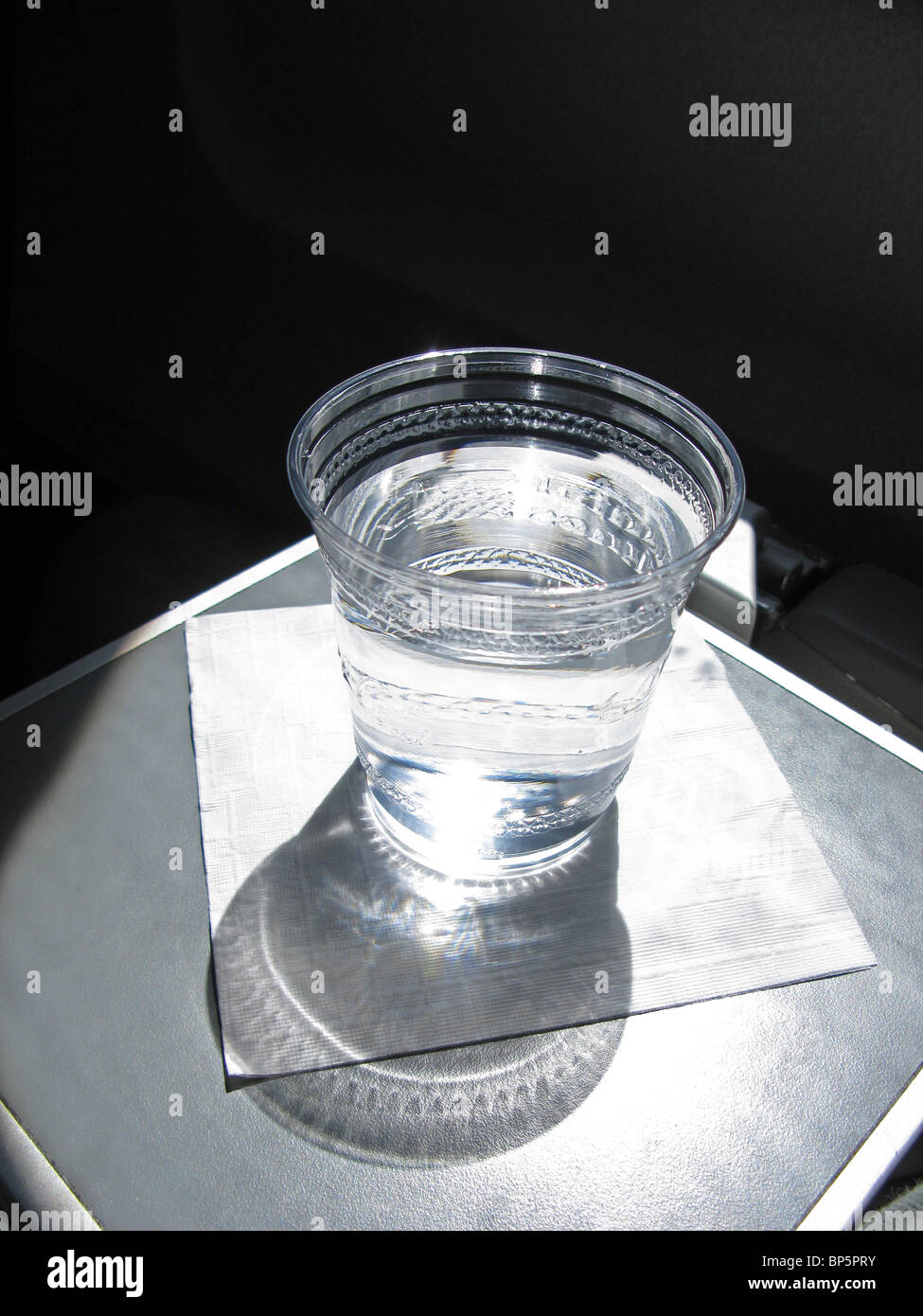 A plastic cup filled with water sitting on a white napkin on a commercial airplane's seat tray with strong window - Stock Image