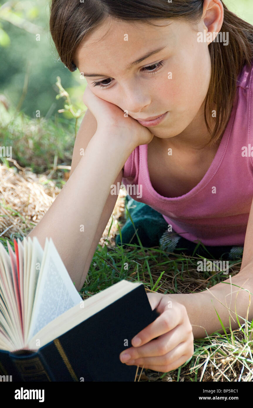 Girls lying on front reading book - Stock Image
