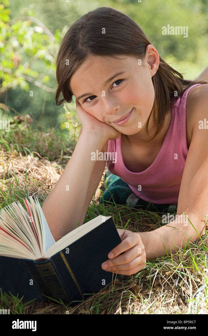 Girls lying on front with book - Stock Image