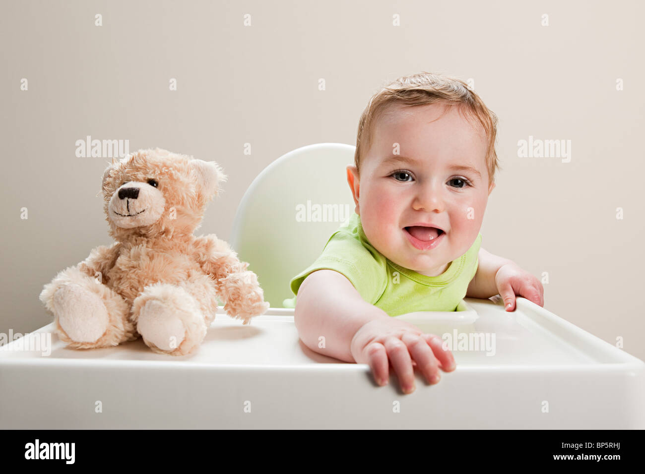 Baby boy sitting in highchair with teddy bear - Stock Image