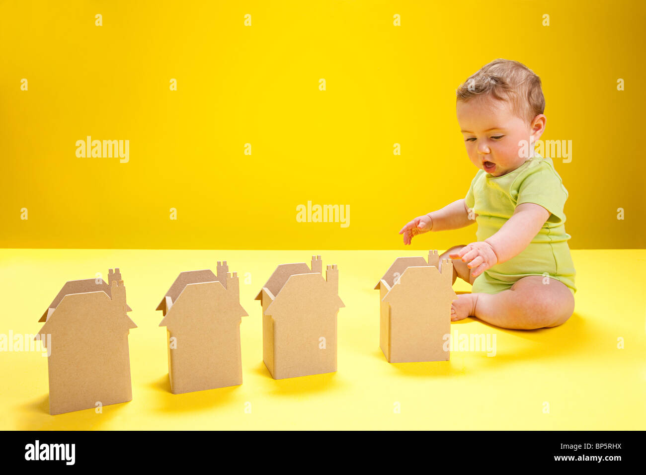 Baby boy playing with cardboard houses - Stock Image