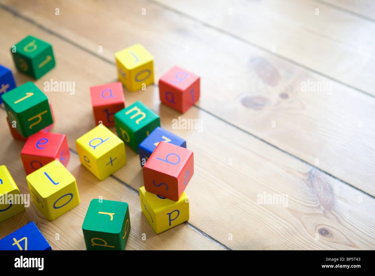 Building blocks on wooden floor - Stock Image