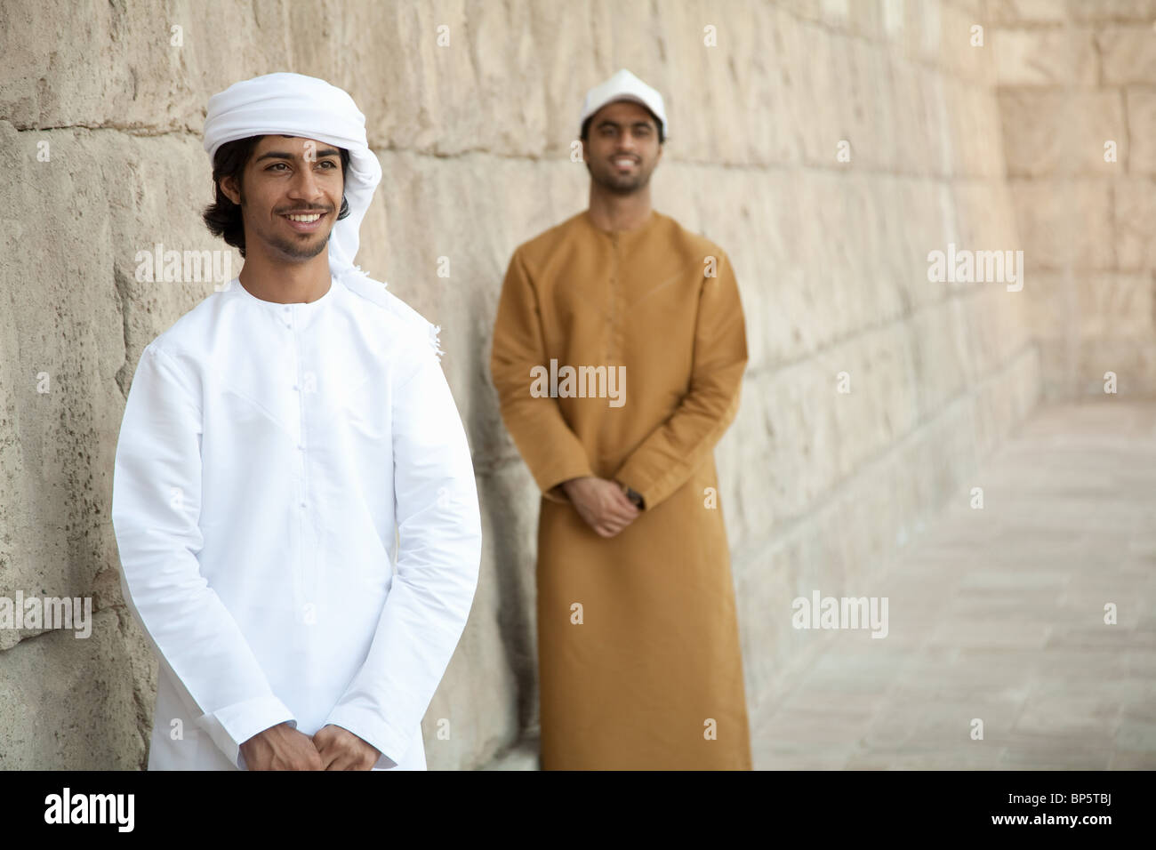 Middle Eastern men looking at by stone wall - Stock Image