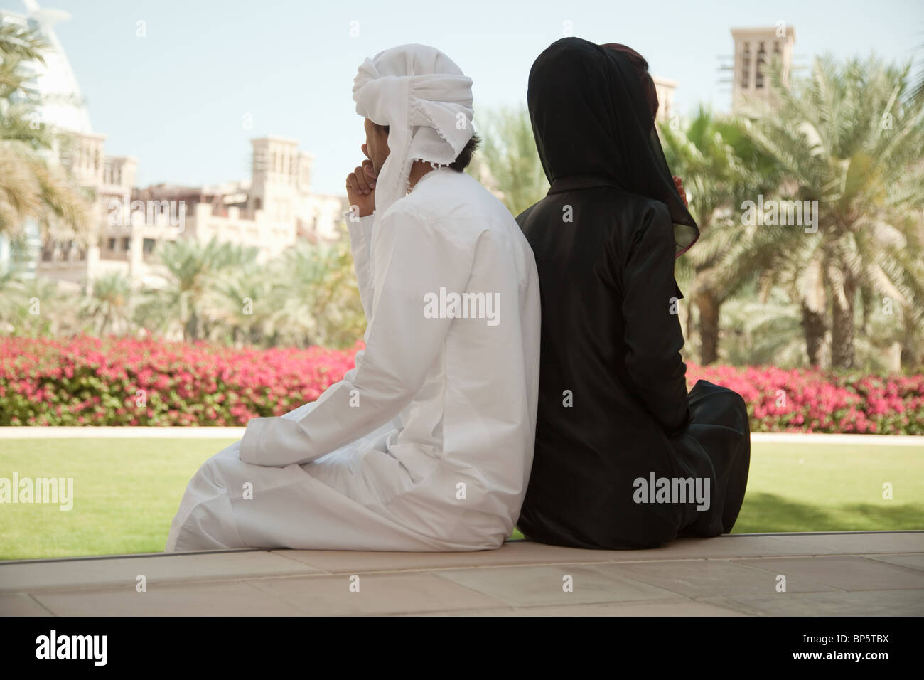 Middle Eastern people sitting side by side - Stock Image
