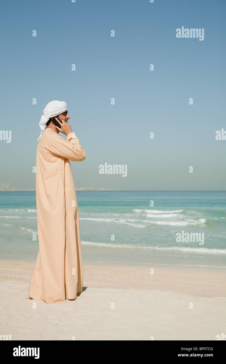 Middle Eastern man using mobile phone on the beach - Stock Image