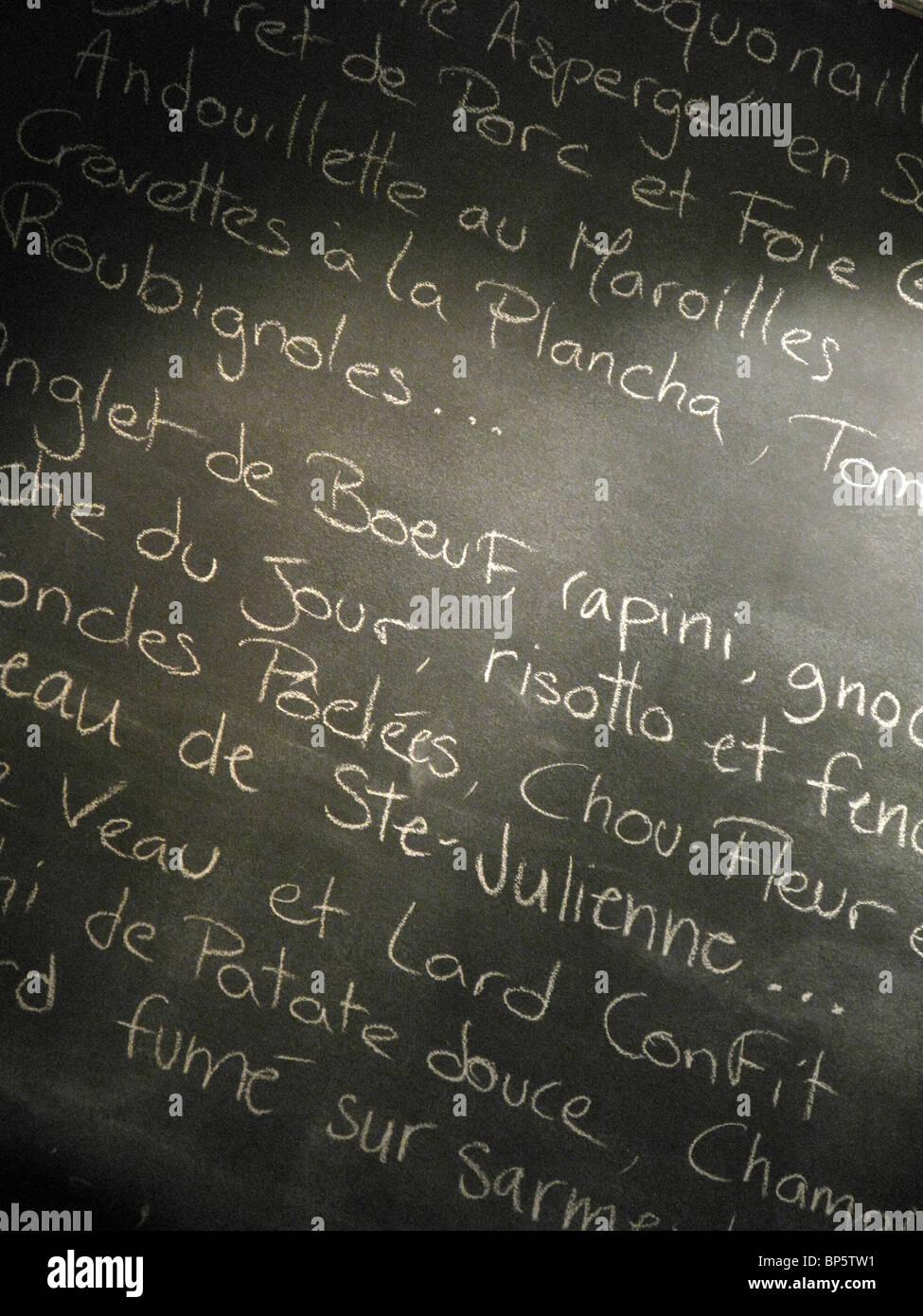A restaurant's menu written in french script on a black chalkboard - Stock Image