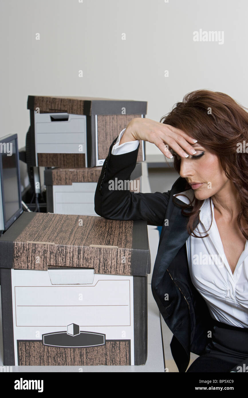 Stressed Businesswoman and Moving Boxes - Stock Image