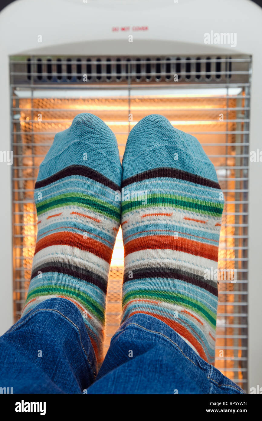 Person wearing colourful matching pair striped woolly socks warming feet in front of a low energy electric Halogen - Stock Image