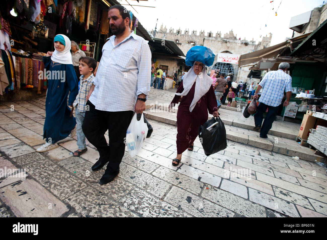Palestinian families, including a woman balancing a bag on her head, walk among the shops of Jerusalem's Old City. Stock Photo