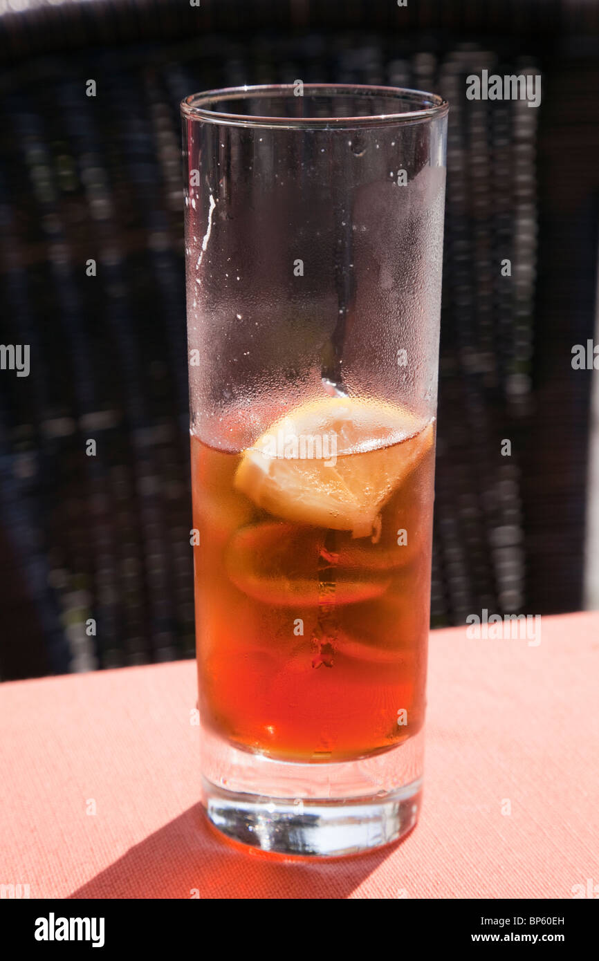 Europe. Half full glass of iced tea with ice cubes and a slice of lemon - Stock Image