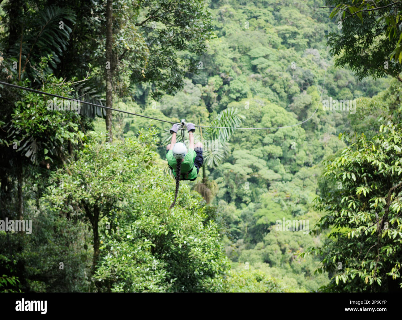 Girl riding a zipline above the rainforest canopy, La Fortuna, Costa Rica - Stock Image