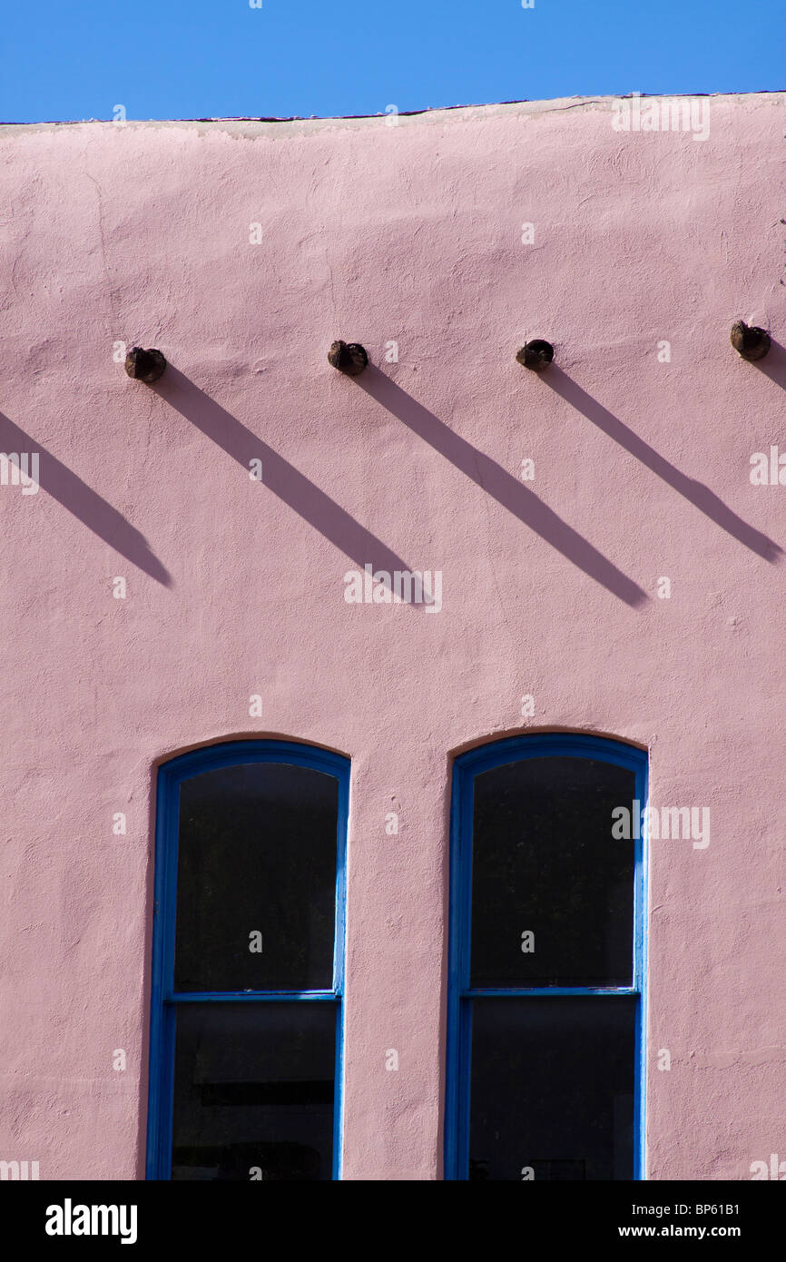 Vigas casting shadows over two windows of a building in the Pueblo revival style of architecture in Santa Fe, New Stock Photo