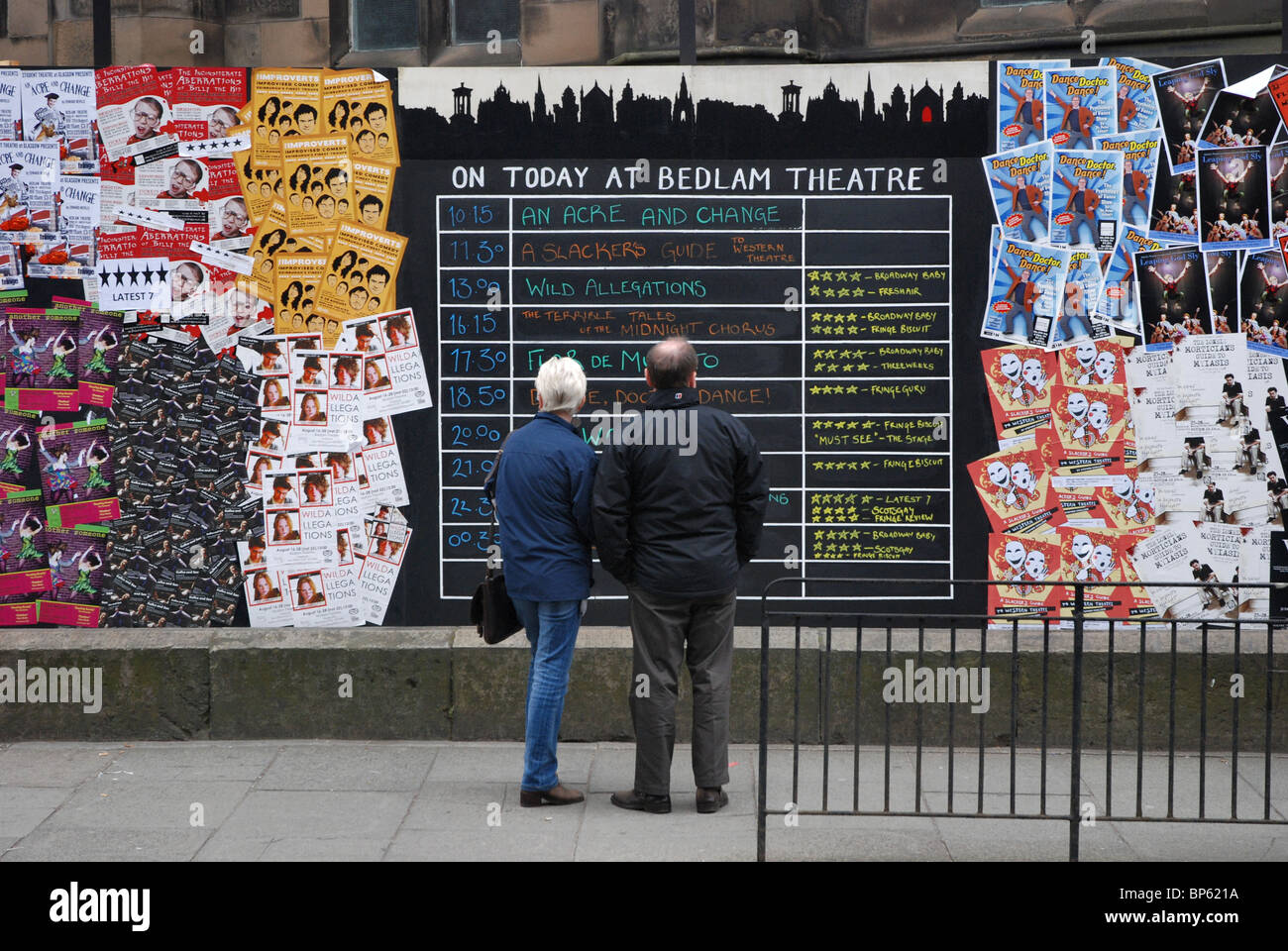 A couple check out the blackboard outside the Bedlam Theatre during the annual Edinburgh Fringe Festival - Stock Image