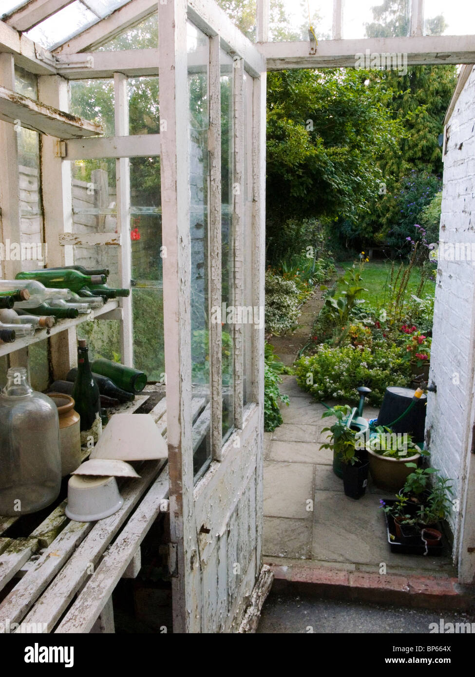 View into cottage garden from old, dilapidated greenhouse. - Stock Image