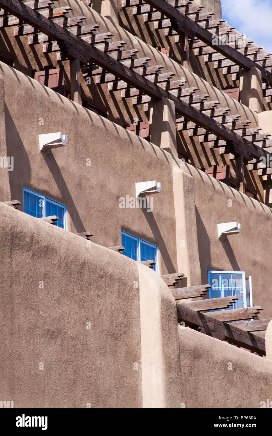 Three windows and many vigas casting shadows on a building in the Pueblo revival style architecture in Santa Fe, Stock Photo