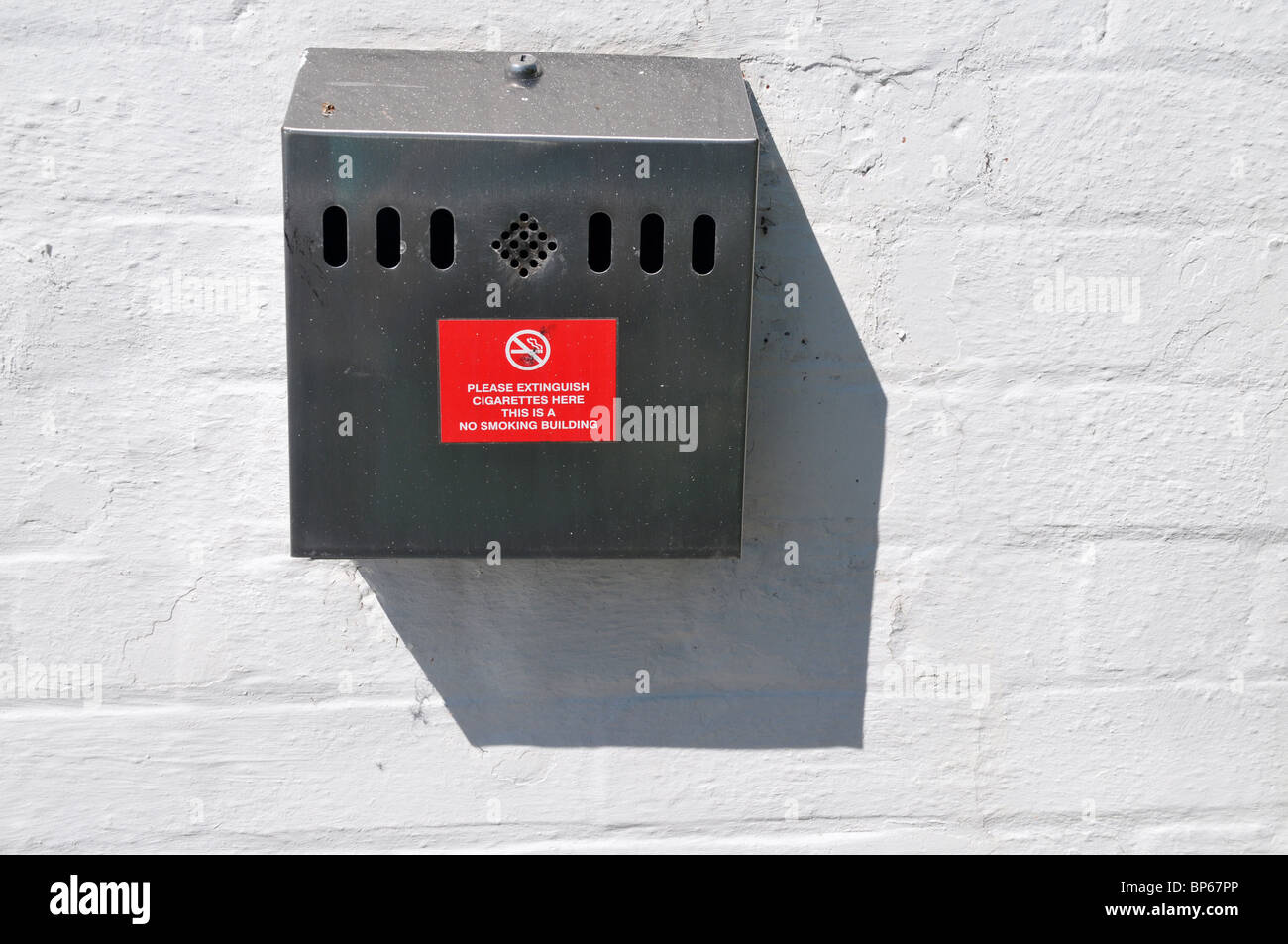 A cigarette extinguisher  bin placed on a wall at the entrance to a no smoking building. - Stock Image