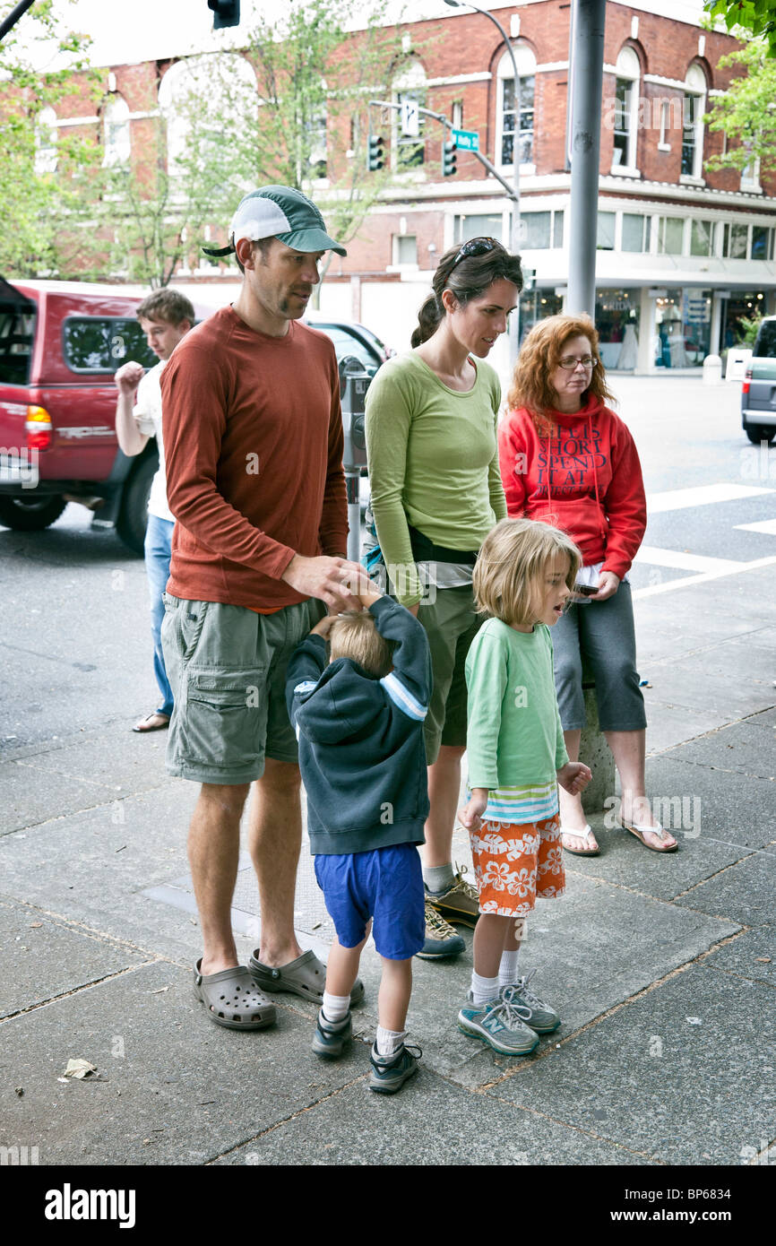 family with small daughter & fidgety younger son admire sidewalk chalk drawings at downtown art festival Bellingham - Stock Image