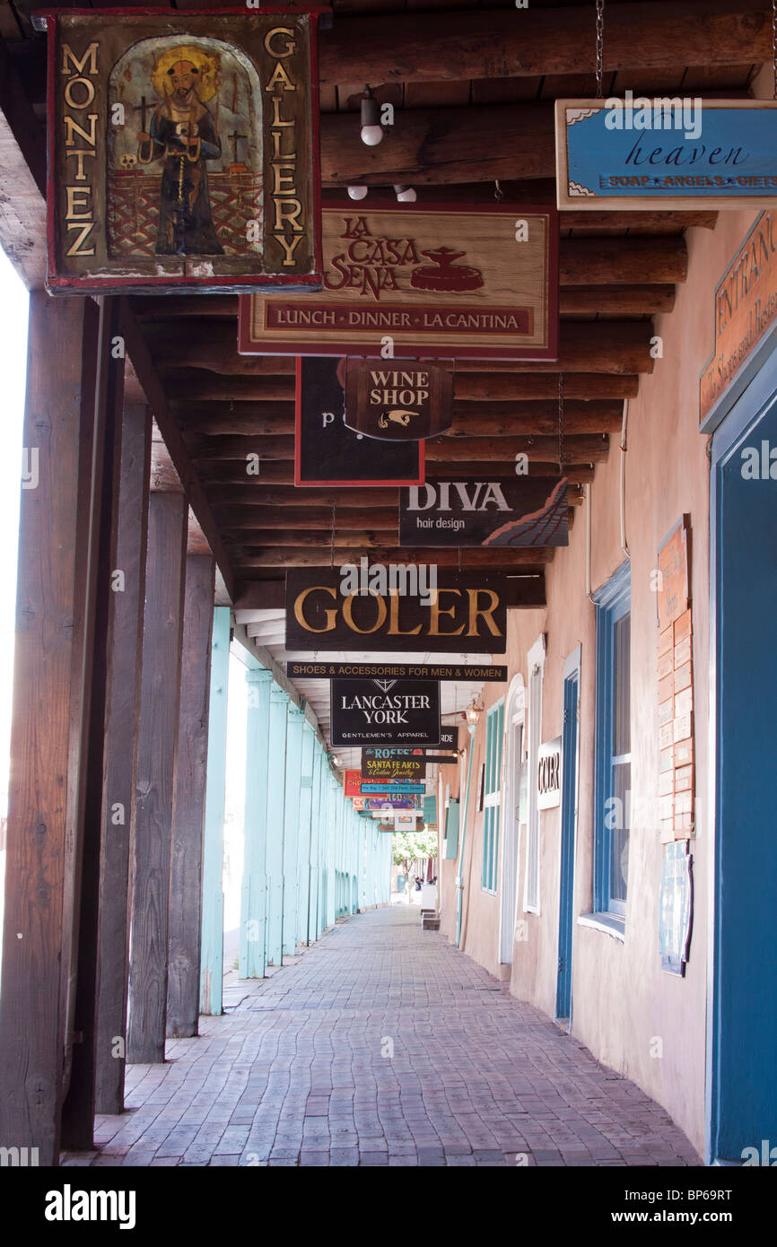 Colorful wood signs for galleries, shops and restaurants line a portico in Santa Fe, New Mexico - Stock Image