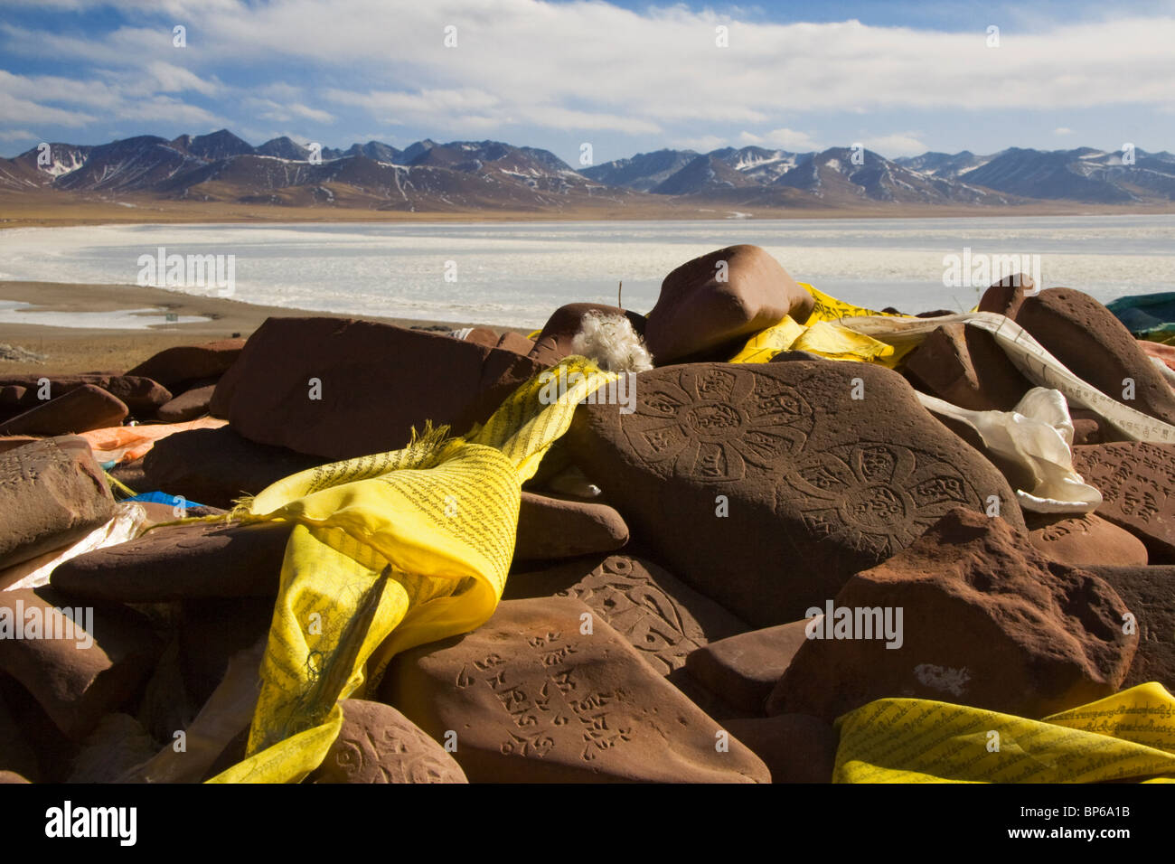 Tibetan prayer flags hug sanskrit engraved stones at the edge of Lake Namsto, Tibet. - Stock Image