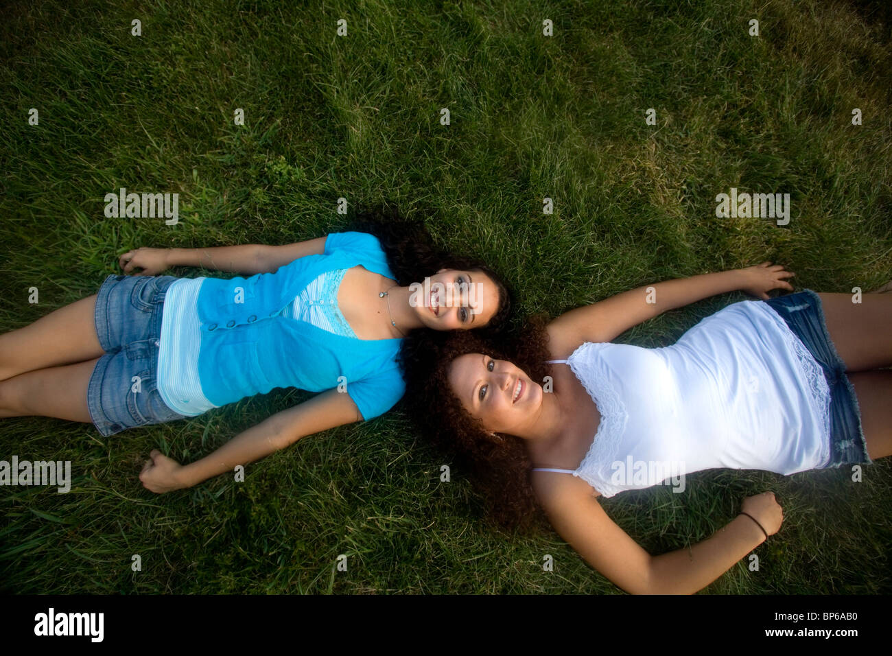 Two cute early twenties caucasian women friends lie in the grass on a summer afternoon - Stock Image