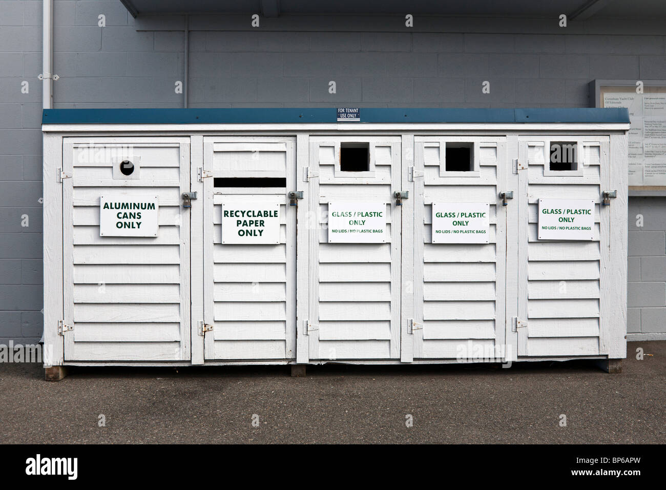 trim neatly labeled white painted wood recycling cabinet with five bins  below a single green formica top at Edmonds - Stock Image