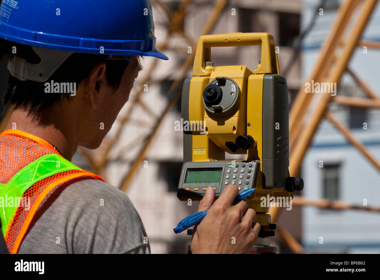 An engineer taking readings off a theodolite on a construction site in Hong Kong. - Stock Image
