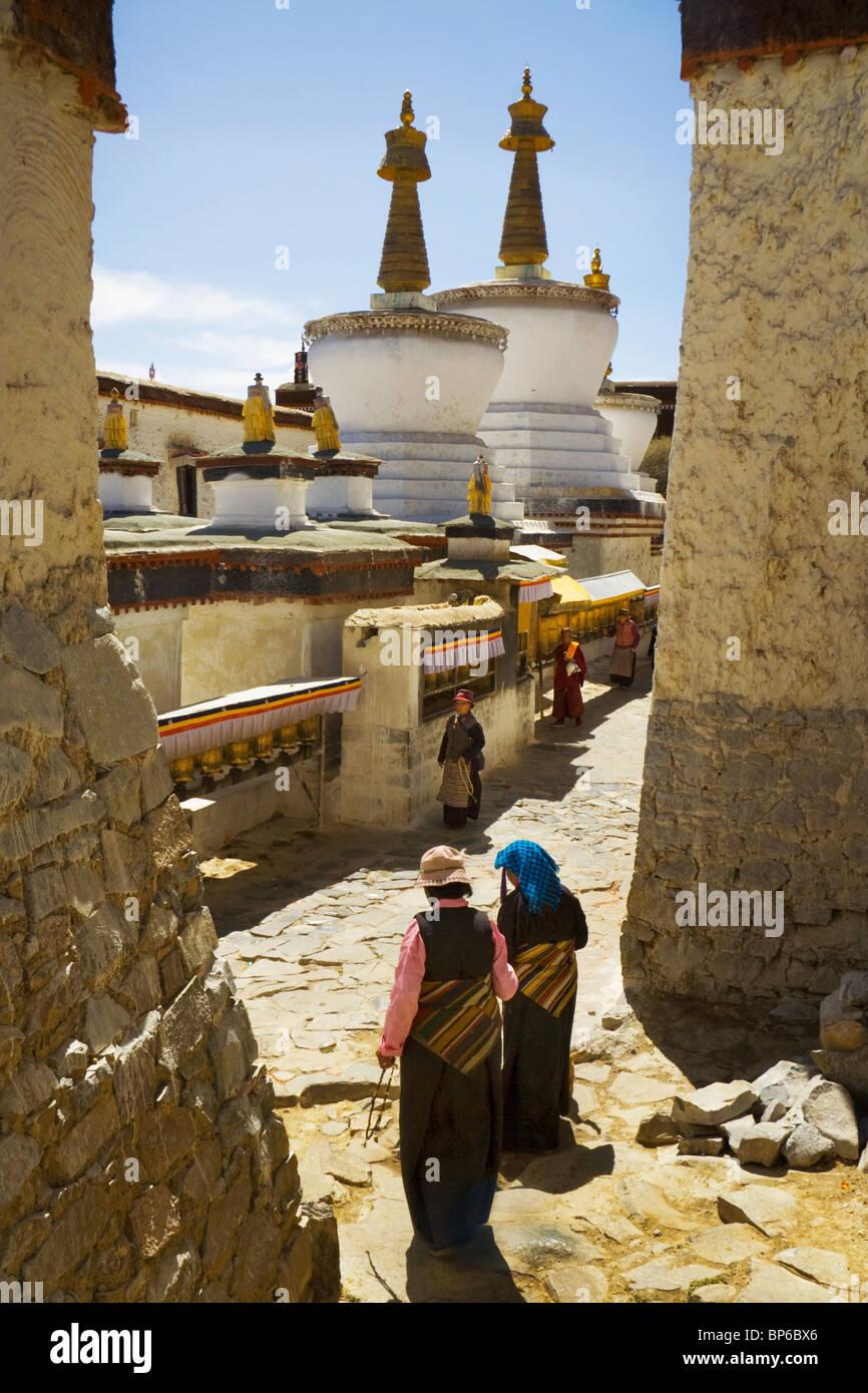 A pilgrim family walk around stupas set in the courtyards of Tashilhunpo monastery in Shigatse, Tibet, China. 2010 Stock Photo
