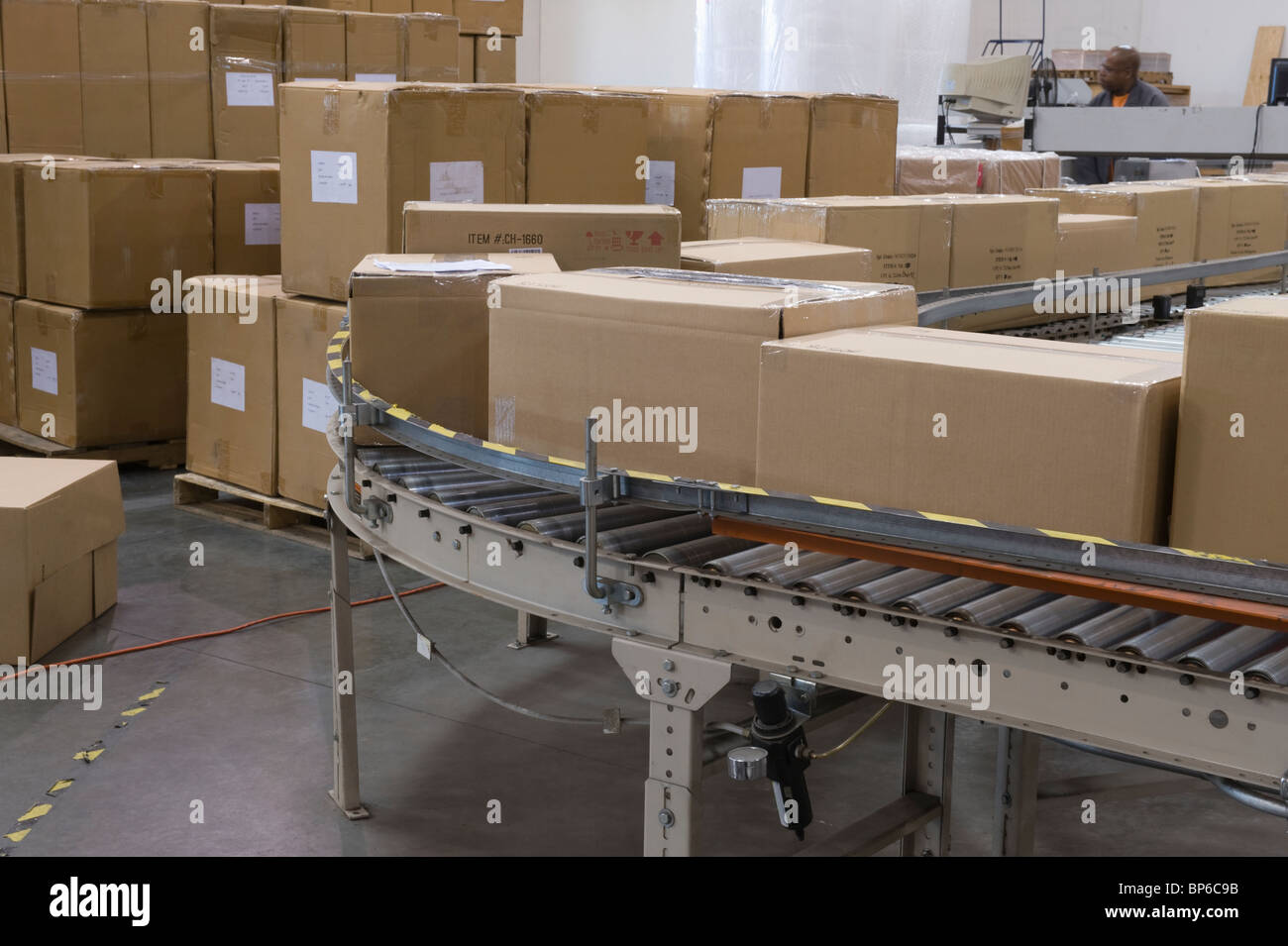 Cardboard boxes on conveyor belt in distribution warehouse - Stock Image