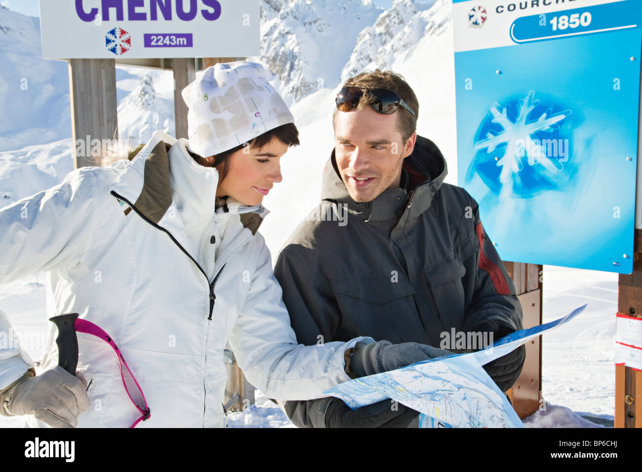 Couple of skiers looking at map, Courchevel, France - Stock Image