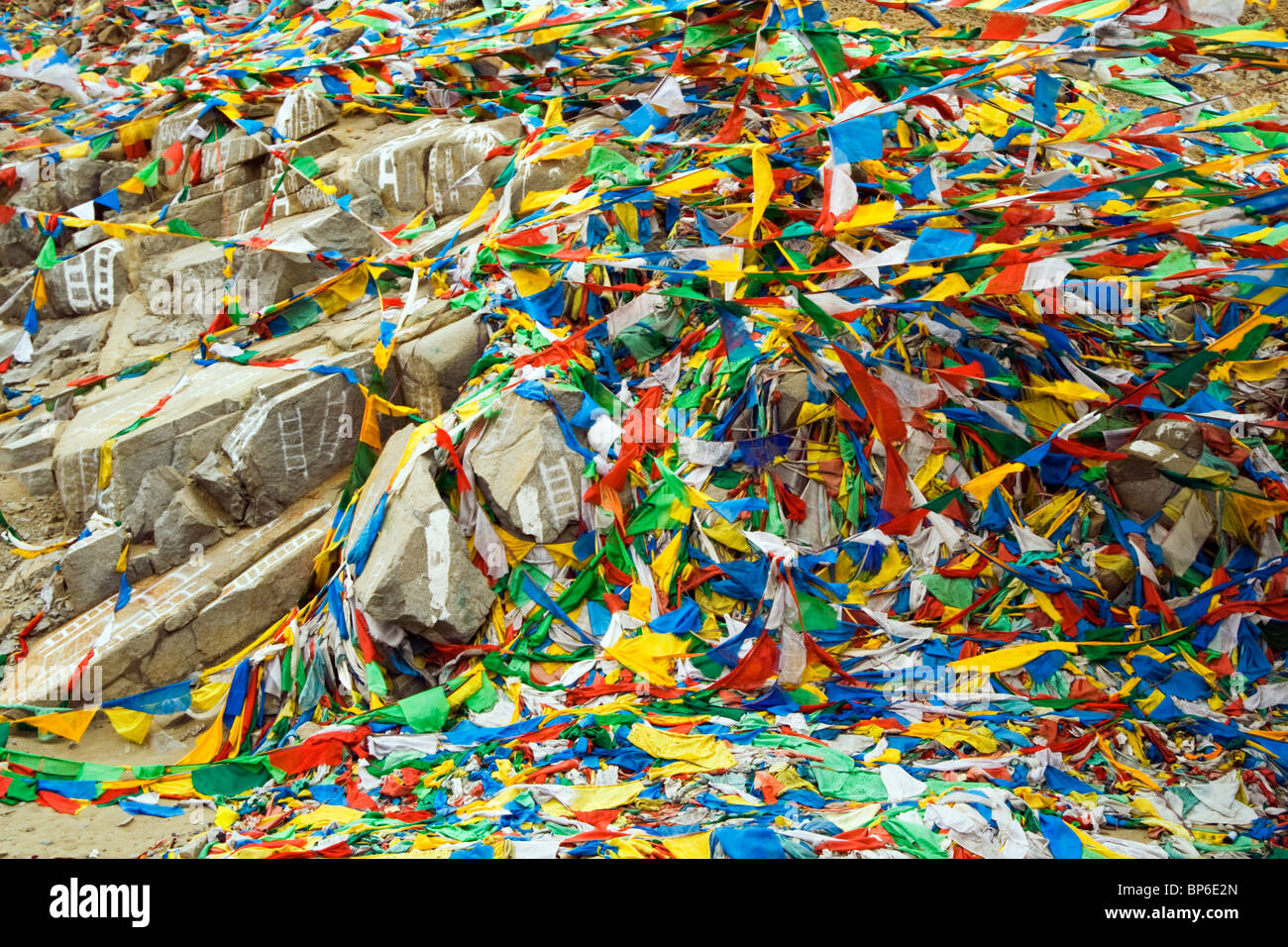 Prayers flags blow against white painted ladders at a Tibetan Burial site - Stock Image
