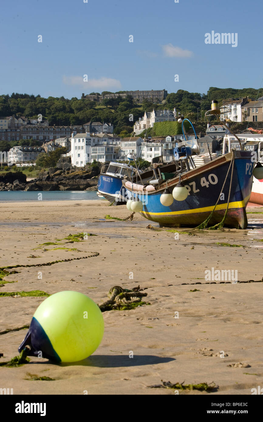 A yellow buoy in front of beached fishing boats in St Ives harbour at low tide. Stock Photo