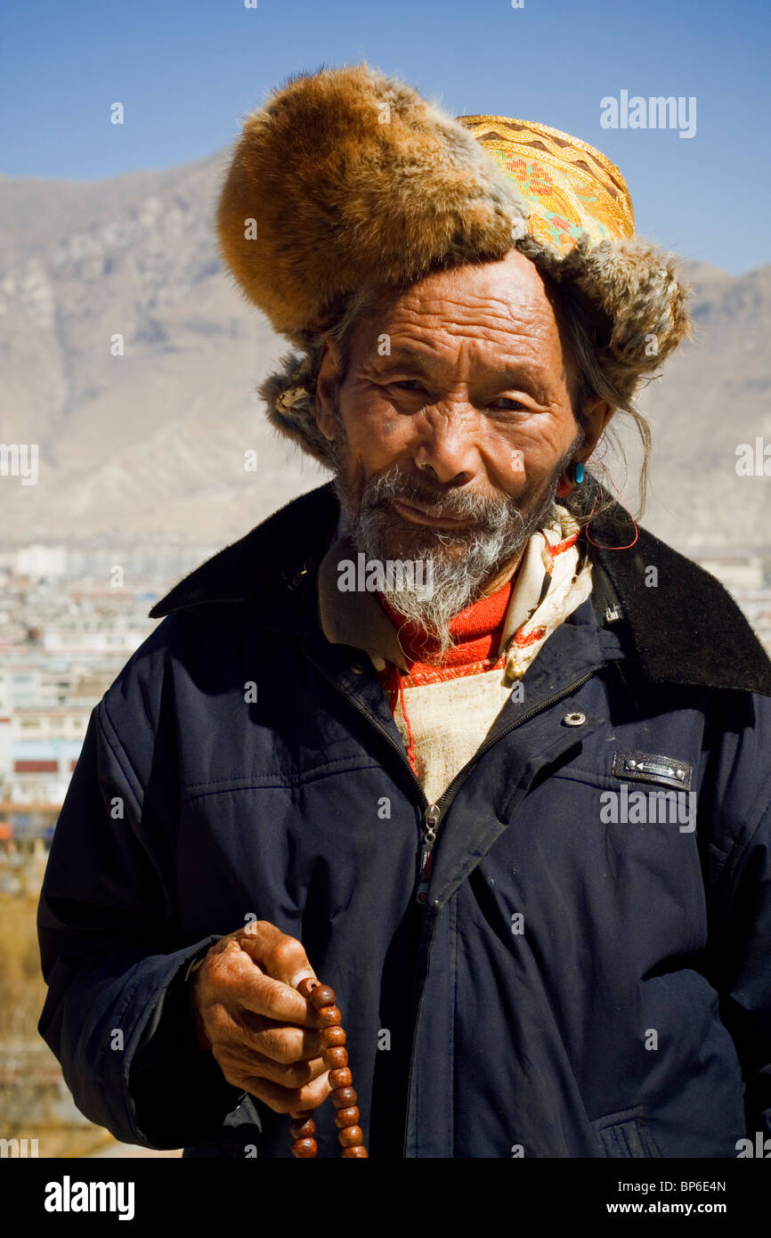 Portrait of a traditionally dressed man on the Potala Palace, in Lhasa, Tibet - Stock Image
