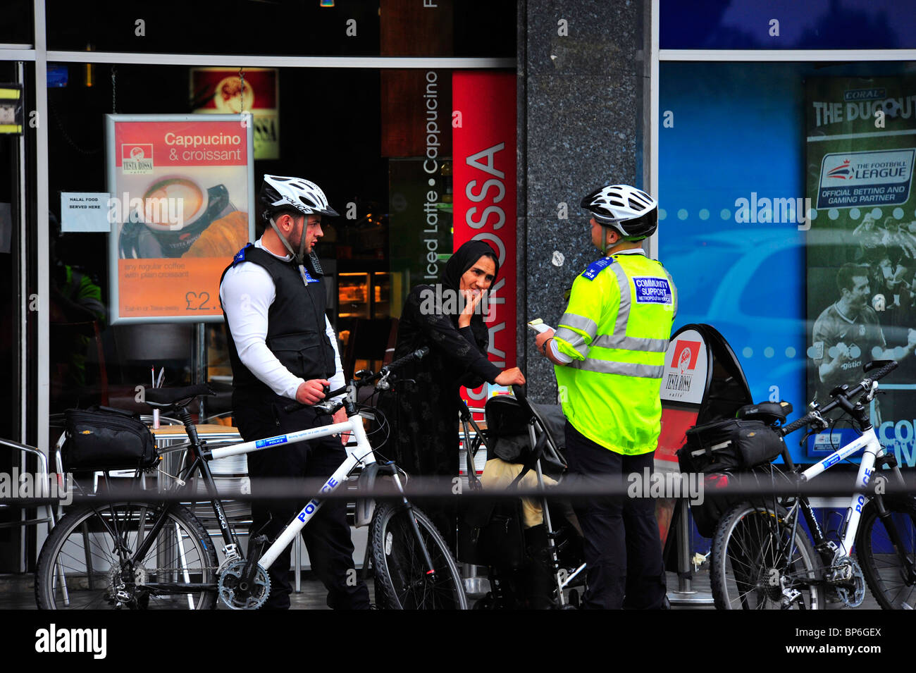 Police community Support Officers stopping a Muslim woman in London - Stock Image