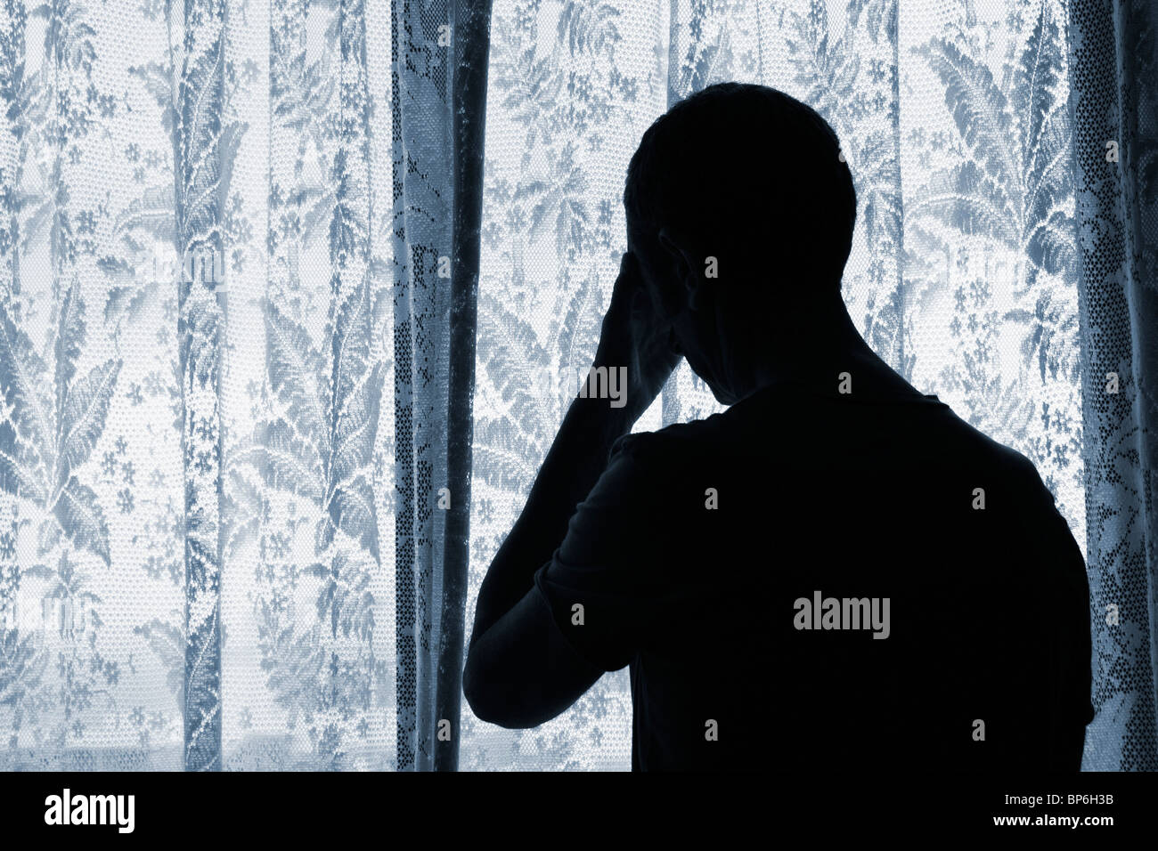 Man looking out of window through net curtains. Image could be used to portray depression, loneliness, agraphobia, - Stock Image